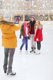 Amis heureux prenant la photo sur la piste de patinage Photos libres de droits