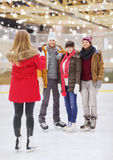 Amis heureux prenant la photo sur la piste de patinage Photo stock