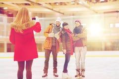 Amis heureux prenant la photo sur la piste de patinage Photographie stock
