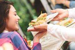 Amis heureux prenant le déjeuner dans le CAM Image stock