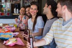 Amis heureux prenant le déjeuner dans le restaurant Photographie stock libre de droits