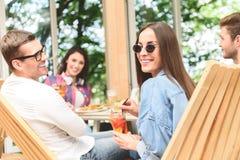 Amis heureux prenant le déjeuner en café Image stock