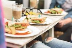 Amis heureux prenant le déjeuner en café Photo stock