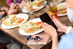 Amis heureux prenant le déjeuner en café Photographie stock