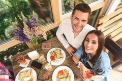 Amis heureux prenant le déjeuner en café Images libres de droits