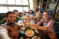 Amis heureux prenant le selfie à la barre ou au bar Images libres de droits