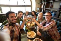 Amis heureux prenant le selfie à la barre ou au bar Image libre de droits