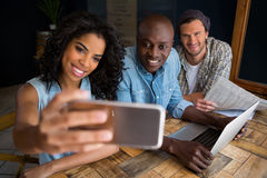 Amis heureux prenant le selfie à la table en bois dans le café Images libres de droits
