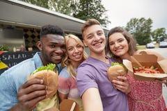 Amis heureux prenant le selfie au camion de nourriture Photos libres de droits