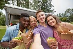 Amis heureux prenant le selfie au camion de nourriture Photos stock