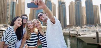 Amis heureux prenant le selfie au-dessus du port de ville Photo stock