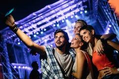 Amis heureux prenant le selfie au festival de musique Photos stock