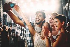 Amis heureux prenant le selfie au festival de musique Photographie stock
