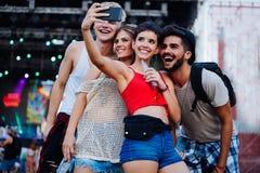 Amis heureux prenant le selfie au festival de musique Images libres de droits