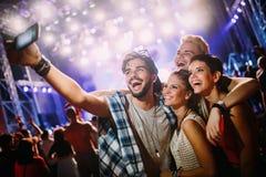 Amis heureux prenant le selfie au festival de musique Images stock