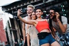 Amis heureux prenant le selfie au festival de musique Photo libre de droits