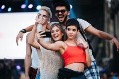 Amis heureux prenant le selfie au festival de musique Image libre de droits