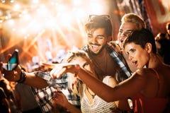 Amis heureux prenant le selfie au festival de musique Image stock