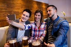 Amis heureux prenant le selfie au restaurant Image stock
