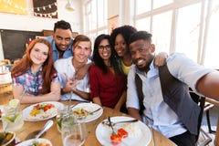 Amis heureux prenant le selfie au restaurant ou à la barre Photos stock
