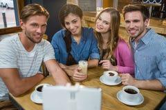 Amis heureux prenant le selfie au téléphone portable tout en ayant le café Photo libre de droits
