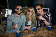 Amis heureux prenant le selfie avec le monopod dans le café Photographie stock