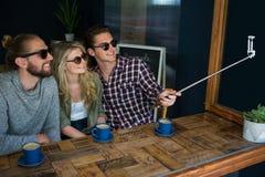 Amis heureux prenant le selfie avec le monopod dans le cafétéria Images stock