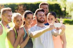 Amis heureux prenant le selfie avec le smartphone Photographie stock