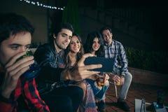 Amis heureux prenant le selfie avec un smartphone en partie Photo stock