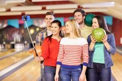 Amis heureux prenant le selfie dans le club de bowling Image stock