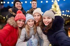 Amis heureux prenant le selfie dehors à Noël Image stock