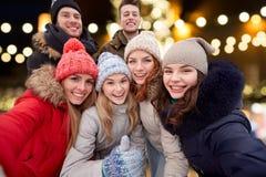 Amis heureux prenant le selfie dehors à Noël Image libre de droits