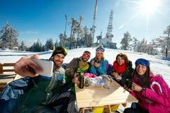 Amis heureux prenant le selfie en café à la station de sports d'hiver Photo libre de droits