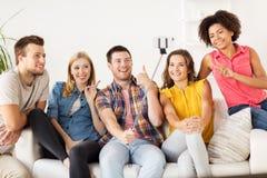 Amis heureux prenant le selfie par le smartphone à la maison Images libres de droits