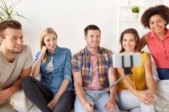 Amis heureux prenant le selfie par le smartphone à la maison Photos stock