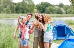 Amis heureux prenant le selfie par le smartphone au camp Image libre de droits