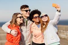 Amis heureux prenant le selfie par le smartphone dehors Photographie stock libre de droits