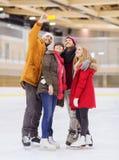 Amis heureux prenant le selfie sur la piste de patinage Photographie stock