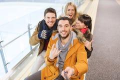 Amis heureux prenant le selfie sur la piste de patinage Image libre de droits
