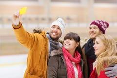 Amis heureux prenant le selfie sur la piste de patinage Photographie stock libre de droits