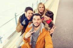 Amis heureux prenant le selfie sur la piste de patinage Images stock