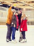 Amis heureux prenant le selfie sur la piste de patinage Photos stock