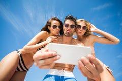 Amis heureux prenant le selfie sur la plage Image stock