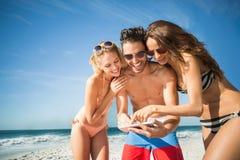 Amis heureux prenant le selfie sur la plage Images stock