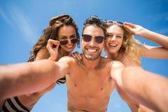 Amis heureux prenant le selfie sur la plage Photographie stock