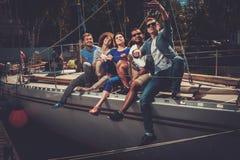 Amis heureux prenant le selfie sur un yacht Images stock