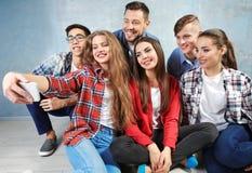 Amis heureux prenant le selfie tout en se reposant sur le plancher Photographie stock
