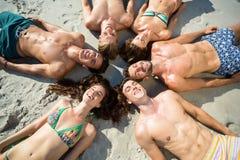 Amis heureux prenant un bain de soleil sur le rivage à la plage Images stock