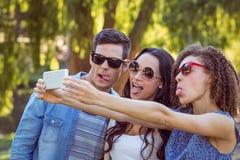 Amis heureux prenant un selfie en parc Images libres de droits