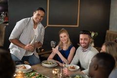 Amis heureux résonnant ensemble dans le restaurant Photographie stock libre de droits